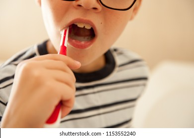 Happy boy washes his hands with soap and brushes his teeth in bathroom. Child loves water and hygiene procedures. Water activities for children. Hygiene and skin care for children. Bathroom interior