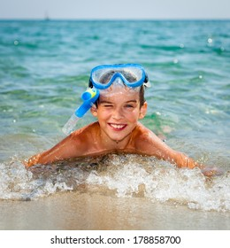 Happy boy wearing snorkeling gear lying in the sea