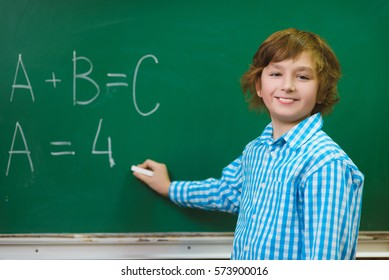 Happy boy writing on blackboard background. Educational and school concept