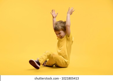 Happy boy in yellow clothes sitting and rising hands up at camera against yellow background
