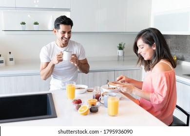 Happy boyfriend drinking coffee while girlfriend applying jam on bread during breakfast