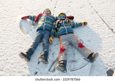 Happy boys in colorful winter clothes doing gymnastics on ice and snow. Glasses for skiing, snowboarding and sledging. A child is playing outdoors in the snow. Outdoor fun for winter holidays