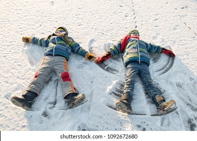 Happy boys in colorful winter clothes doing gymnastics on ice and snow. Glasses for skiing, snowboarding and sledging. Child is playing outdoors in snow. Outdoor fun for winter holidays. Snow angels