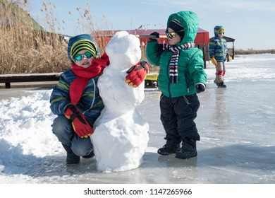 Happy boys in colorful winter clothes doing gymnastics on ice and snow. Glasses for skiing, snowboarding and sledging. child is playing outdoors in snow. Outdoor fun for winter holidays
