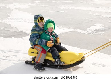 Happy boys enjoy sledding. Yellow children's sled. The kid is riding a sleigh. Children playing outdoors in the snow. In winter, children ride on a frozen lake. Outdoor fun for family winter vacations
