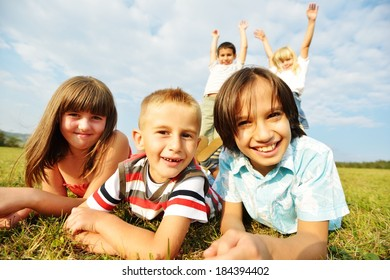 Happy boys and girls sitting on summer grass meadow