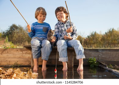 Happy boys go fishing on the river , Two children fisher with a fishing rod on the shore of the lake