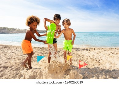 Happy boys making sandcastle together on the beach