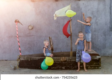Happy boys play pirates and seafarers. Three brothers have fun together. The old boat is decorated with balloons.