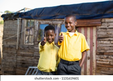 Happy boys with their thumbs up while standing infront of a shack.