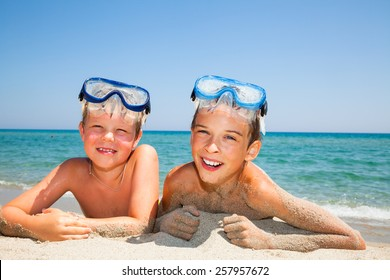 Happy boys wearing snorkeling gear relaxing on the beach