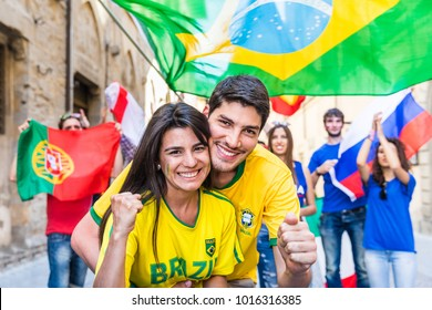 Happy Brazilian couple supporters celebrating victory. Fans from other countries enjoying sport together. Sport, respect and fair play concepts