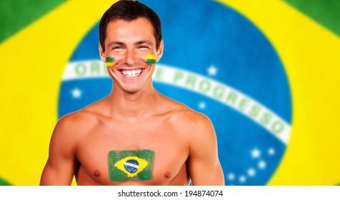 Happy brazilian fan standing over brazil flag background