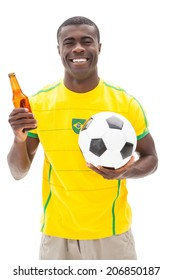 Happy brazilian football fan holding ball and beer on white background