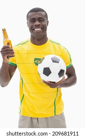 Happy brazilian football fan in yellow holding beer and ball on white background