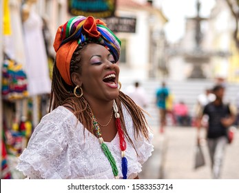 Happy Brazilian woman of African descent dressed in traditional Baiana costumes in the Historic Center of Salvador da Bahia, Brazil. - Shutterstock ID 1583353714