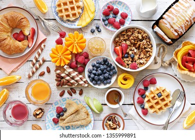 Happy breakfast with granola, croissant, fresh waffles, fruits and berries.