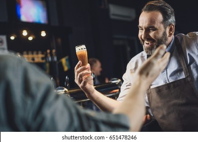 Happy brewery worker holding small glass of beer