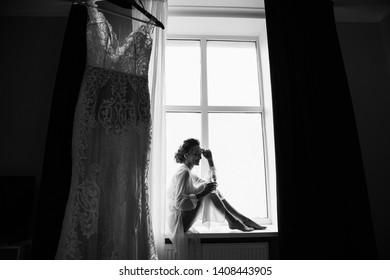 Happy bride with champagne glass near wedding dress