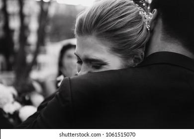 Happy bride crying on groom's shoulder