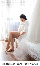 Happy bride dressing up by putting on sheer stockings on a wedding morning. Wedding dress hem and veil can be seen  on the right