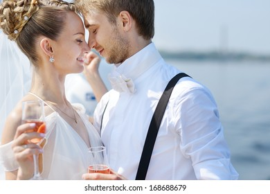 Happy bride and groom drinking champagne on a yacht