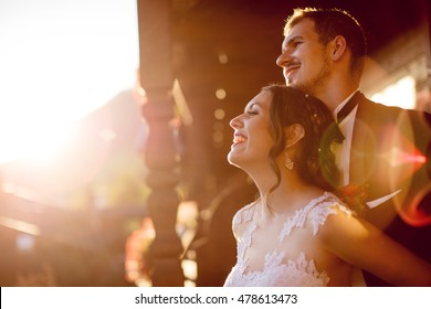 Happy bride and groom enjoying the view from balcony during sunset.