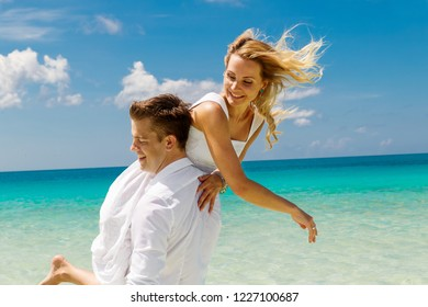 Happy Bride and Groom having fun on the tropical beach. Tropical sea and palm boats in the background. Wedding and honeymoon concept.