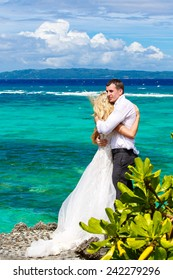 Happy bride and groom having fun on a tropical beach under the palm trees. Tropical sea in the background. Summer vacation concept.