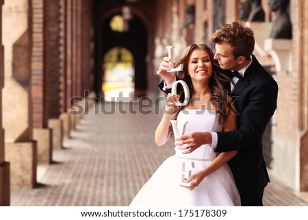 happy bride and groom holding love letters