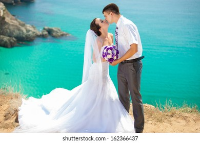 Happy bride and groom hugging on cliff on the background of the sea