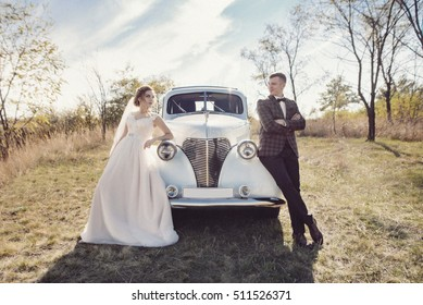 Happy bride and groom hugging and posing near old retro car before wedding ceremony