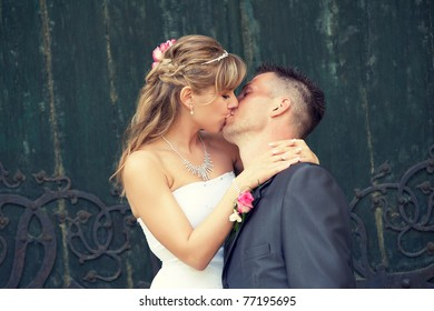 Happy bride and groom kissing on the stairs