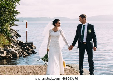 happy bride and groom at a near to lake on their wedding day
