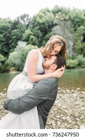 Happy bride and groom on the river bank