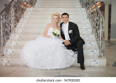 Happy bride and groom on staircase at wedding walk