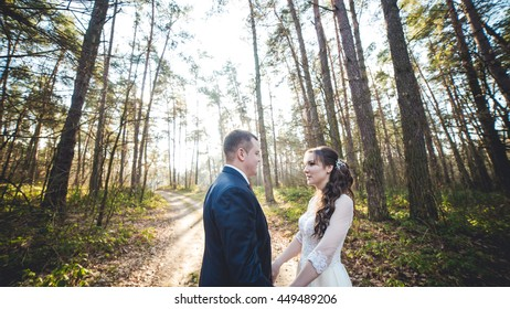 Happy bride and groom in a park. Wedding couple