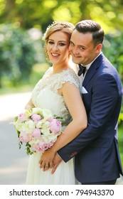 Happy bride and groom posing in park. Birde holding bouquet of flowers in hands