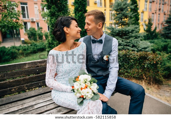 Happy bride and groom sitting on bench on wedding day