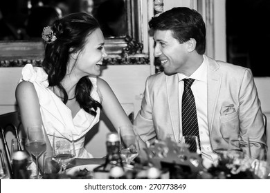 happy bride and groom smiling  look et each other in a restaurant