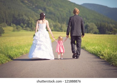happy bride and groom with their daughter walking on the road