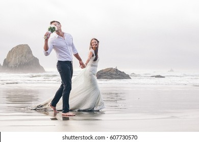 Happy bride and groom walk by the beach