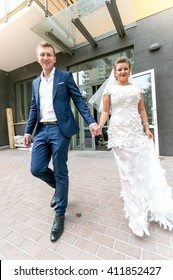 Happy bride and groom walking on street and holding hands