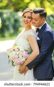 Happy bride and groom walking in park. Birde holding bouquet of flowers in hands