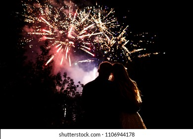 Happy bride and groom watching beautiful colorful fireworks on night sky. Wedding couple at night wedding ceremony