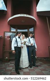 Happy bride with groom's best men are posing