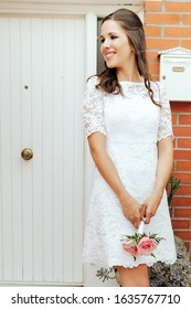 Happy bride holding her small wedding bouquet of pink roses in white door. Wedding day concept.