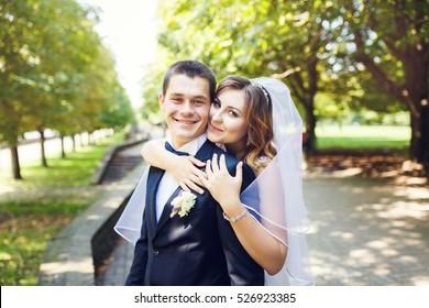 Happy bride hugs the groom in the summer park