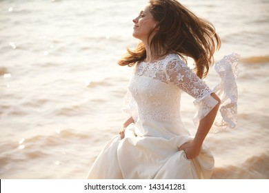 Happy bride in lace dress running near waterline