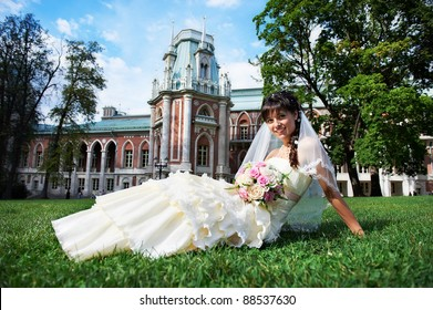 Happy bride on grass in summer park on background palace
